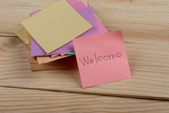 """Greeting concept - The text """"Welcome"""" written by hand on sticker on wooden background. Communication, information, message, paper, reminder, word royalty free stock photos"""