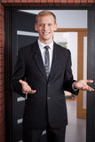 Greeting customers. Young handsome realtor greeting customers in new house Stock Photos