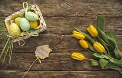 Greeting easter composition on a wood. Top view of bouquet of flowers, colored eggs in the box and holiday felicitation Royalty Free Stock Photos