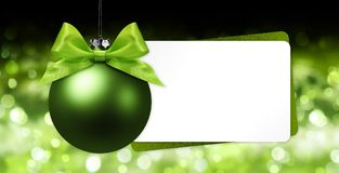 Greeting gift card with green christmas ball on blurred lights b Royalty Free Stock Images