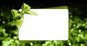 Greeting gift card with green ribbon bow  on blurred chr Royalty Free Stock Photo