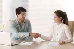 Greeting handshake of businesswoman and businessman sitting in b stock photos