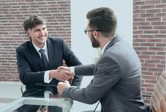 Greeting handshake of colleagues at the desk. Welcoming handshake of colleagues. Business people and business partnership royalty free stock photo
