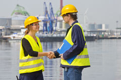 Greeting harbor workers. Two dockers greeting eachother in an industrial harbor, wearing the necessary safety gear Stock Photos