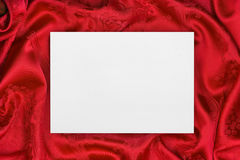 Greeting paper card on red cloth Royalty Free Stock Photo