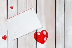 Greeting paper card and three red hearts on wooden white background with copy space royalty free stock images