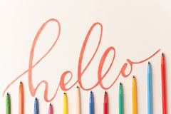 Greeting phrase handwritten with orange marker. Greeting motivational colorful phrase `Hello` handwritten with orange marker on white paper. Top view of Stock Image