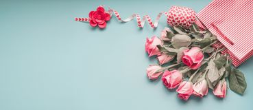 Greeting pink pale roses bunch in shopping bag with ribbon on turquoise blue background, top view Stock Images