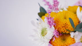 Greeting video card. Close-up of a bouquet of flowers, rotation on a white background. The flower arrangement consists of Chrysanthemum Chamomile, Santini stock video footage