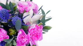 Greeting video card. Close-up of a bouquet of flowers, rotation on a white background. The flower arrangement consists of feverweed, Carnation, eucalyptus stock video footage