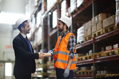 Greeting of workers. Happy foreman in helmet greeting one of warehouse workers Royalty Free Stock Photography