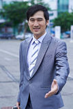 Greeting you. Smiling Vietnamese businessman with luggage outstretching hand for a handshake Stock Images