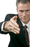 Greetings. Man in business suite offering his hand in a posture of greeting or agreement Royalty Free Stock Images
