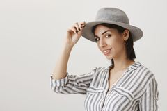 Greetings cowboy. Portrait of emotive woman in stylish striped blouse holding hat to salute or greet friend as if royalty free stock photos