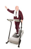 Greetings at the Gym. Senior man on the treadmill waves to a friend at the gym.  Isolated on white Royalty Free Stock Images