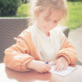 Greetings from holiday. Girl writing greetings on postcard Royalty Free Stock Photos