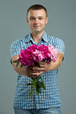 Greetings. Man giving bouquet of flowers. Young beautiful enamored man casual style with flowers. Royalty Free Stock Photos