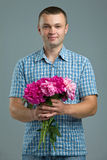 Greetings. Smiling man casual style with flowers. Stock Photos