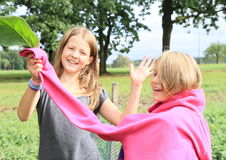 Greetings. Young brunette girl - smiling kid in grey t-shirt holding pink sleeve of pull of blond laughing girl with green leaf and waving hand for greetings on Stock Photo