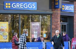 Greggs the Bakers, with customers sitting outside and a man walking out with Greggs take away food and a hot drink. UK. March 7 19 stock image