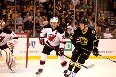 Gregory Campbell and Bryce Salvadore (NHL Hockey). Gregory Campbell (#11) of the Boston Bruins in front of New Jersey Devils defenseman Bryce Salvador #24 Royalty Free Stock Images