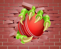 Greifer mit dem Kricketball, der durch Backsteinmauer bricht Stockbild