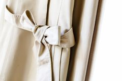 Greige or beige elegant trench coat with ribbon isolated over white. A greige or beige elegant trench coat with ribbon isolated over white.Close up stock photo
