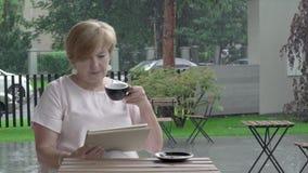 Greisin an der Terrasse liest eine Tablette und genießt eine Tasse Tee Starker Regen stock video