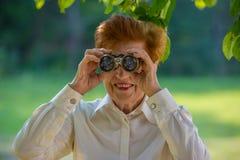 Greisin, die durch Ferngläser in einem Park schaut Lizenzfreies Stockbild