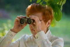 Greisin, die durch Ferngläser in einem Park schaut Stockfotografie