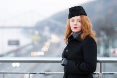 Greisin im schwarzen Mantel an der Brückensperre Portrait der städtischen Frau Herbst mag Rougefrauen stockbilder
