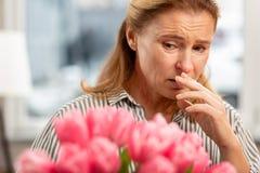 Greisin mit den Gesichtsfalten, die schlecht sich fühlen, Allergie zu den Tulpen habend stockfoto