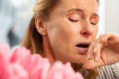 Greisin mit Gesichtsfalten niesend, nachdem Blumenstrauß gerochen worden ist lizenzfreie stockfotografie