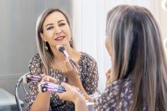 Greisin setzt an ihr Make-up Schauen im Spiegel selbst ein Maskenbildner, der Pulver auf dem Gesicht mit einer großen Bürste anwe stockbild