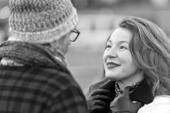 Greisin untersucht Manngesicht Glückliche Dame hören Geschichte in den Gläsern und im Hut zu bemannen Frauengespräche, Treffen de lizenzfreies stockbild