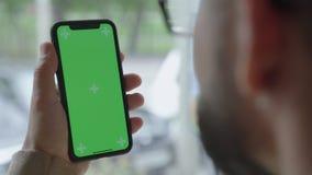 Grej skärm med en grön skärm Mannen rymmer telefonen med en hand lager videofilmer