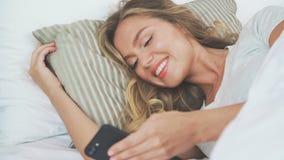 Grejer i säng: flickan använder en mobiltelefon på läggdags Hon ligger på sida arkivfilmer