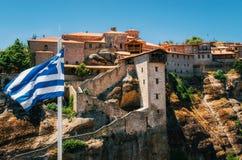 Grekisk flagga framme av den heliga kloster av stora Meteoron i Meteora, Grekland Royaltyfri Foto