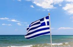 Grekisk flagga, hav och kust i bakgrund crete greece Arkivfoto