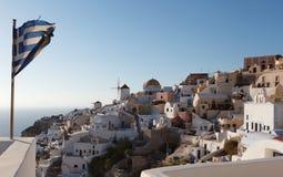 Grekisk flagga i den Oia byn på den Santorini ön Royaltyfria Bilder