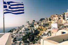 Grekisk flagga i den Oia staden - Santorini Arkivbild