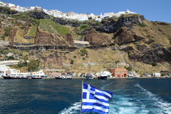 Grekisk flagga med hamnen av Thira Fira och Thira på överkanten av arkivfoton