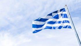 Grekisk flagga och molnig himmel i sommardagen, politik av Europa arkivbild