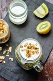 Grekisk frukost för yoghurtgranolakiwi i krus Arkivfoton