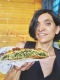 Grekisk kvinna som äter en traditionell Spanakotiropita, spenat- och Fetapaj royaltyfri foto