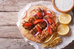 Grekisk mat: Souvlaki med grönsaker och pitabröd horisontal Royaltyfri Bild