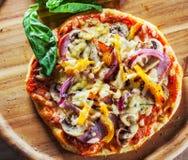 Grekisk pizza med champinjoner, skinka, ost, lökar, peppar royaltyfri bild