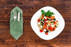 Grekisk sallad av den nya gurkan, tomaten, söt peppar, grönsallat, den röda löken, fetaost och oliv med olivolja Sunt arkivbild