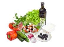 Grekisk sallad bland ingredienser för dess matlagning på ljus backgroun arkivbild
