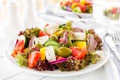 grekisk sallad Sallad för ny grönsak med tomat-, lök-, gurka-, peppar-, oliv-, grönsallat- och fetaost grekisk plattasallad Arkivfoton